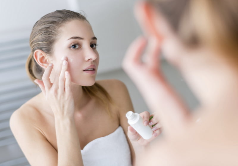 young woman applying skin cream to her face