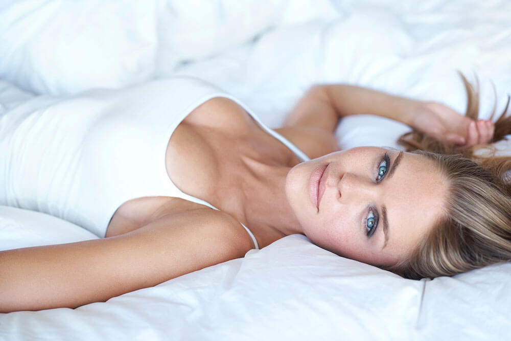 woman-laying-on-white-bed
