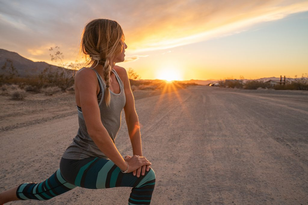Woman stretching before early morning run