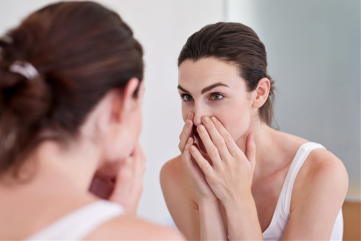 Woman Examines Her Nose for a Deviated Septum in the Mirror